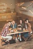 Amigos jovenes felices que disfrutan de la comunicación en café Foto de archivo libre de regalías