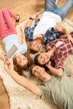 Amigos jovenes felices que mienten en la alfombra y que toman el selfie Fotografía de archivo libre de regalías