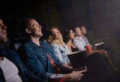 Amigos jovenes felices que miran película en cine imagenes de archivo