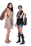 Amigos jovenes felices que se colocan con los bolsos de compras Imagenes de archivo