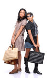 Amigos jovenes felices que se colocan con los bolsos de compras Foto de archivo
