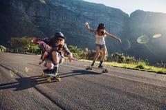 Amigos jovenes felices que se divierten con el monopatín Imagenes de archivo