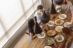 Amigos jovenes felices que sientan y que cenan en la cocina Foto de archivo libre de regalías