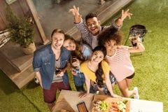 Amigos jovenes felices que sonríen en la cámara en la comida campestre Imagenes de archivo