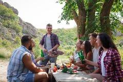 Amigos jovenes felices que tienen comida campestre en el parque Son todos felices, divirtiéndose, sonriendo Adultos jovenes Comid Fotografía de archivo