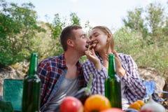 Amigos jovenes felices que tienen comida campestre en el parque Son todos felices, divirtiéndose, sonriendo Adultos jovenes Comid Fotos de archivo libres de regalías