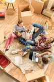 Amigos jovenes felices que usan el ordenador portátil en la alfombra en nueva casa Imagen de archivo