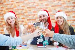 Amigos jovenes hermosos del primer que tintinean los vidrios en la Navidad en un fondo borroso Concepto de las vacaciones de invi Imágenes de archivo libres de regalías