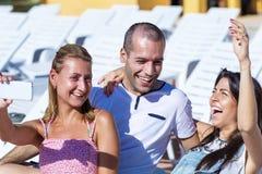Amigos jovenes hermosos que ríen y que hacen el selfie en la piscina Imágenes de archivo libres de regalías