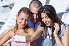 Amigos jovenes hermosos que ríen y que hacen el selfie en la piscina Fotografía de archivo