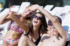 Amigos jovenes hermosos que ríen y que hacen el selfie en la piscina Fotos de archivo