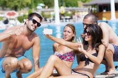 Amigos jovenes hermosos que se divierten que hace el selfie en la piscina Foto de archivo libre de regalías