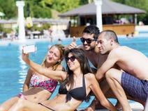 Amigos jovenes hermosos que se divierten que hace el selfie en la piscina Imágenes de archivo libres de regalías