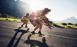 Amigos jovenes longboarding abajo del camino Foto de archivo