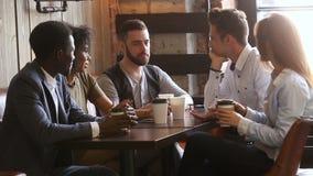 Amigos jovenes multinacionales que comen café de consumición de la diversión en la tabla del café almacen de video