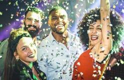 Amigos jovenes multirraciales que bailan en el club de noche del partido Foto de archivo libre de regalías