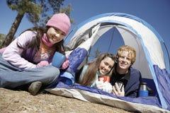 Amigos jovenes por la tienda en el sitio para acampar Fotografía de archivo