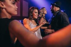Amigos jovenes que bailan en club de noche Imagen de archivo