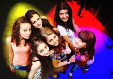 Amigos jovenes que bailan en un club de noche Imagen de archivo