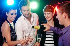 Amigos jovenes que beben el champán en barra del disco Fotos de archivo libres de regalías