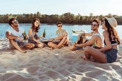 Amigos jovenes que beben la cerveza mientras que se relaja en la playa arenosa en la orilla imagen de archivo