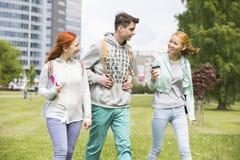Amigos jovenes que caminan en el campus de la universidad imagen de archivo libre de regalías