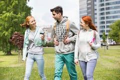 Amigos jovenes que caminan en el campus de la universidad Imágenes de archivo libres de regalías