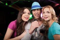 Amigos jovenes que cantan en el micrófono en el partido Foto de archivo libre de regalías