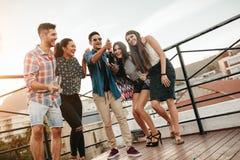Amigos jovenes que celebran con champán en el partido imágenes de archivo libres de regalías