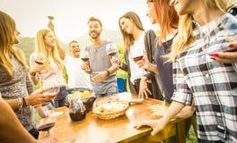 Amigos jovenes que comen vino rojo de consumición al aire libre de la diversión - peopl feliz imagen de archivo