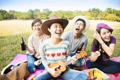 amigos jovenes que disfrutan de comida campestre y que juegan el ukelele Foto de archivo libre de regalías