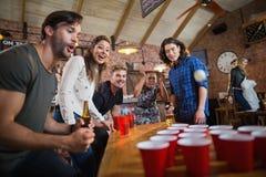 Amigos jovenes que disfrutan del juego del pong de la cerveza en restaurante Imagenes de archivo