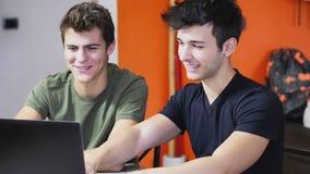 Amigos jovenes que exploran el ordenador portátil Foto de archivo