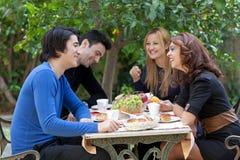 Amigos jovenes que gozan del café en un restaurante Fotografía de archivo
