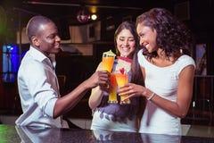 Amigos jovenes que gozan mientras que teniendo cóctel bebe en el contador de la barra imagen de archivo
