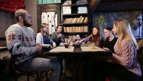 Amigos jovenes que hacen la pila de teléfonos elegantes en café almacen de video