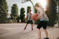 Amigos jovenes que juegan a baloncesto en corte Fotografía de archivo