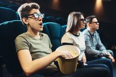 Amigos jovenes que miran la película 3d en cine Imagenes de archivo