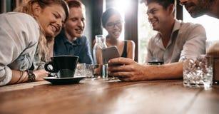 Amigos jovenes que miran las fotos en el teléfono móvil imagen de archivo libre de regalías
