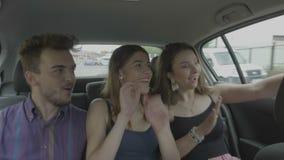 Amigos jovenes que montan el coche del uber del taxi a través de la ciudad que toma imágenes del selfie con el teléfono móvil que almacen de metraje de vídeo