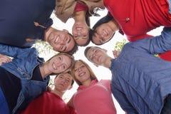 Amigos jovenes que permanecen junto al aire libre en el parque Imagenes de archivo