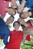 Amigos jovenes que permanecen junto al aire libre en el parque Fotos de archivo