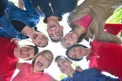 Amigos jovenes que permanecen junto al aire libre en el parque Foto de archivo