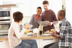 Amigos jovenes que preparan el desayuno en cocina Fotos de archivo