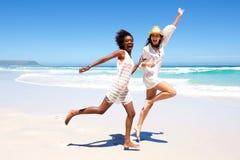 Amigos jovenes que ríen y que corren en la playa Imagen de archivo libre de regalías