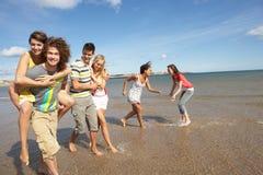 Amigos jovenes que recorren a lo largo de línea de la playa del verano Fotografía de archivo