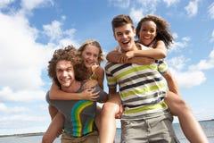 Amigos jovenes que se divierten en la playa del verano Foto de archivo libre de regalías