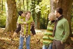 Amigos jovenes que se divierten en parque del otoño Foto de archivo libre de regalías