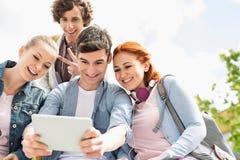Amigos jovenes que se fotografían a través de la tableta digital en el campus de la universidad Imagen de archivo