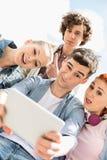 Amigos jovenes que se fotografían a través de la tableta digital en el campus universitario Fotos de archivo libres de regalías